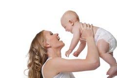 La sonrisa rubia de la madre de la belleza y toma al bebé Imágenes de archivo libres de regalías