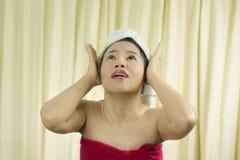 La sonrisa temporaria de la mujer, triste, divertida, lleva una falda para cubrir su pecho después del pelo del lavado, envuelto imagen de archivo libre de regalías