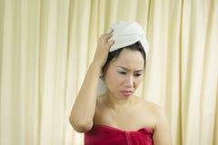 La sonrisa temporaria de la mujer, triste, divertida, lleva una falda para cubrir su pecho después del pelo del lavado, envuelto imagenes de archivo