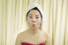 La sonrisa temporaria de la mujer, triste, divertida, lleva una falda para cubrir su pecho después del pelo del lavado, envuelto imagen de archivo