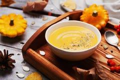La sopa caliente de la calabaza adornó las semillas y el tomillo en el cuenco blanco en la tabla de madera rústica Forma de vida  Imágenes de archivo libres de regalías