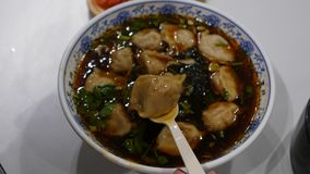 La sopa de Damplings en el cuenco, mano de la mujer con la cuchara revuelve la comida caliente metrajes