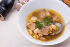 La sopa de habas en la placa blanca con la cuchara del metal, varias tuesta en pizca Imagen de archivo libre de regalías