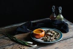 La sopa de la calabaza sirvió en calabaza, y seta en la placa oscura y cambiante Imagenes de archivo