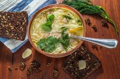 La sopa de pollo con las pastas y las verduras en una arcilla ruedan imagenes de archivo