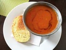 La sopa del tomate con la tostada del ajo, primer del servicio de la sopa de los mariscos del tomate con pan en un cuenco en la p Fotos de archivo