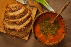 La sopa nutritiva sirvió con el cuenco de madera integral del pan n Fotografía de archivo libre de regalías