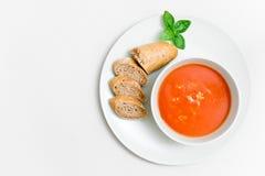 La sopa fresca del tomate con pequeño pan y la albahaca hojean en una placa con el fondo texturizado papel Foto de archivo