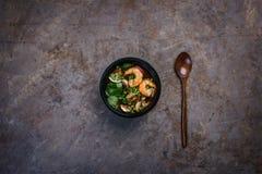 La sopa tailandesa picante Tom Yam con los mariscos en un cuenco negro en un vintage coloreó el fondo con una cuchara de madera V imagen de archivo