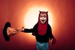 La sorcière de Halloween avec un potiron et une magie découpés s'allume dans un jeu d'enfants de forêt d'obscurité avec les potir images libres de droits