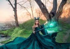 La sorcière stricte avec le personnel magique magique de rougeoyer et miroiter dans des ses mains, dame avec des klaxons sur la  photos libres de droits
