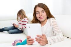 La sorella amici scherza le ragazze che giocano con il pc della compressa in sofà Fotografia Stock