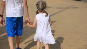 La sorella che tiene la mano di suo fratello più anziano, i bambini cammina dal mare un giorno soleggiato, un'infanzia felice video d archivio