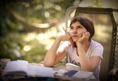 La sorella dei fratelli germani dei bambini dell'adolescente aiuta suo fratello con il compito di compito Fotografie Stock