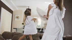 La sorella due nel salto bianco del vestito sul sofà si diverte il combattimento con i cuscini molli nel salone a casa Due svegli archivi video