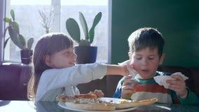 La sorella preoccupantesi pulisce il fronte del fratello con il tovagliolo durante la cena alla pizzeria video d archivio