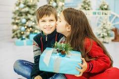 La sorellina bacia il fratello Il ragazzo e la ragazza Cristo felice Fotografia Stock