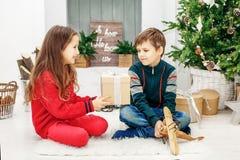 La sorellina presenta un regalo a suo fratello Natale felice Fotografie Stock Libere da Diritti
