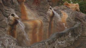 La sorgente di acqua calda minerale naturale entra fuori in una fontana per la bevanda archivi video