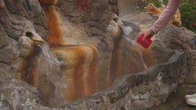 La sorgente di acqua calda minerale naturale entra fuori in una fontana per la bevanda video d archivio