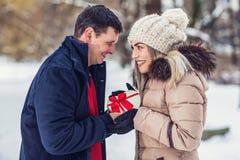 La sorpresa romantica per il Natale, uomo dà una scatola con un regalo a immagini stock libere da diritti