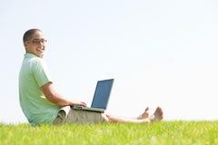 la sosta degli uomini del computer portatile si siede usando i giovani Fotografia Stock