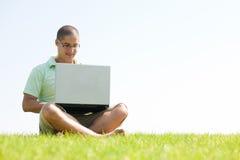 la sosta degli uomini del computer portatile si siede usando i giovani Fotografia Stock Libera da Diritti