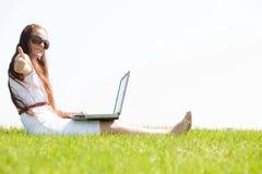 la sosta del computer portatile del feamle si siede usando i giovani Immagine Stock Libera da Diritti
