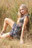 la sosta dell'erba della ragazza sessuale si siede Fotografie Stock Libere da Diritti