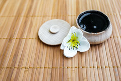 La sostanza nera in un barattolo di legno su un fondo di bambù Immagine Stock