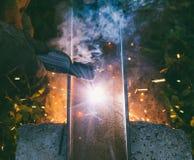 La soudeuse d'ouvrier brûle par un trou d'électrode dans un canal en acier le soir Image libre de droits