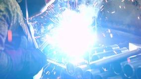 La soudeuse dans un masque protecteur soude des parties à une usine métallurgique banque de vidéos