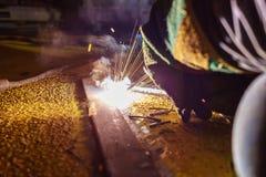 La soudeuse effectuent la soudure à la plaque de métal au plancher de toit du manuf Photographie stock libre de droits