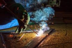 La soudeuse effectuent la soudure à la plaque de métal au plancher de toit du manuf Photo libre de droits