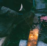 La soudeuse masculine fonctionnante brûle le trou d'électrode dans le canal en acier Photographie stock