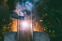 La soudeuse masculine fonctionnante brûle le trou d'électrode dans le canal en acier le soir Photos stock