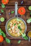 La soupe à crevette de cari a servi dans un pot argenté sur une table brune photographie stock libre de droits