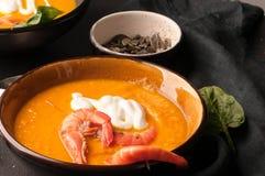 La soupe à potiron avec des crevettes, acidifient dans des cuvettes et pain foncé, verdure et tissu photos stock