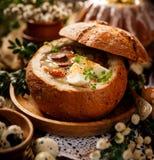 La soupe aigre faite de farine de seigle avec la saucisse et les oeufs a servi dans le bol de pain Soupe aigre polonaise traditio photographie stock libre de droits