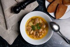La soupe aux fèves dans le plat blanc avec la cuillère en métal, plusieurs grillent sur le petit morceau Photos stock