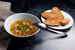 La soupe aux fèves dans le plat blanc avec la cuillère en métal, plusieurs grillent sur le petit morceau Photo stock