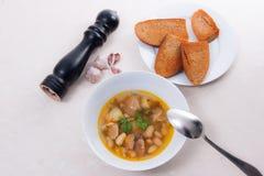 La soupe aux fèves dans le plat blanc avec la cuillère en métal, plusieurs grillent sur le petit morceau Photo libre de droits