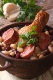 La soupe avec des haricots, les jambes de poulet et les saucisses se ferment vers le haut de la verticale Photo libre de droits