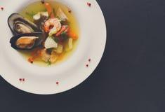 La soupe française à fruits de mer avec les poissons blancs, les crevettes et les moules plat dedans Image libre de droits