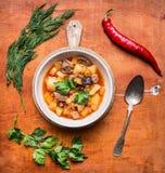 La soupe épicée avec l'agneau et les légumes, pommes de terre dans des plats blancs administrent le poivron à la cuillère rouge é Images stock