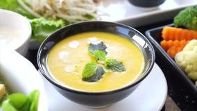 La soupe visuelle à potiron arrangent sur le repas en bois de table avec l'autre nourriture végétale saine clips vidéos
