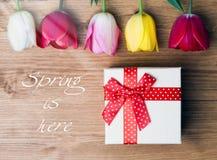 La source est ici Boîte-cadeau et tulipes sur le fond en bois Photographie stock
