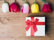 La source est ici Boîte-cadeau et tulipes sur le fond en bois Photos stock