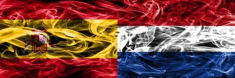 La Spagna contro le bandiere olandesi del fumo disposte parallelamente Colo spesso Immagine Stock