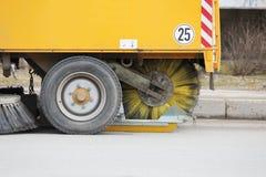 La spazzatrice urbana gialla libera la strada dalla sporcizia con una spazzola rotonda in primavera fotografia stock